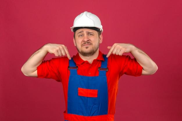Builder homme portant des uniformes de construction et un casque de sécurité pointant vers le bas à la triste et bouleversé indiquant la direction avec les doigts sur le mur rose isolé