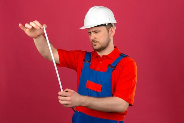 Builder homme portant des uniformes de construction et un casque de sécurité à la recherche de ruban de mesure dans les mains avec un visage sérieux debout sur un mur rose isolé