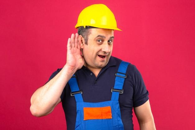 Builder homme portant des uniformes de construction et casque de sécurité souriant avec la main sur l'oreille à l'écoute d'une audition sur mur rose isolé