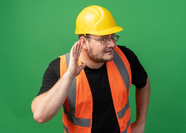 Builder man in construction gilet et casque de sécurité tenant la main sur l'oreille essayant d'écouter à l'air intrigué