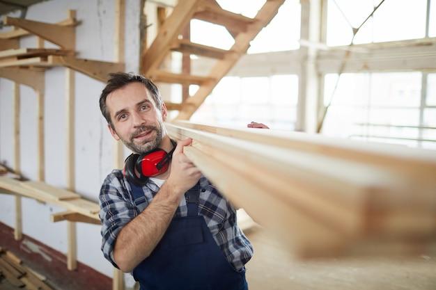 Builder mature transportant des planches de bois
