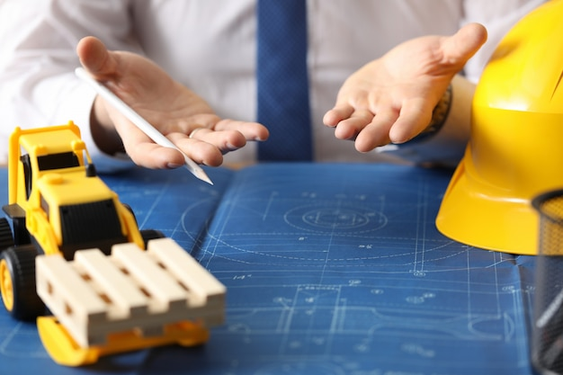 Builder tenant un crayon et montrant le plan