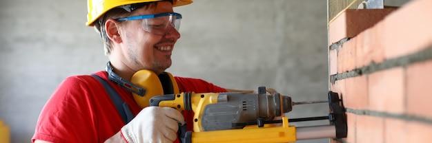 Builder trou de forage dans le mur, chantier de construction