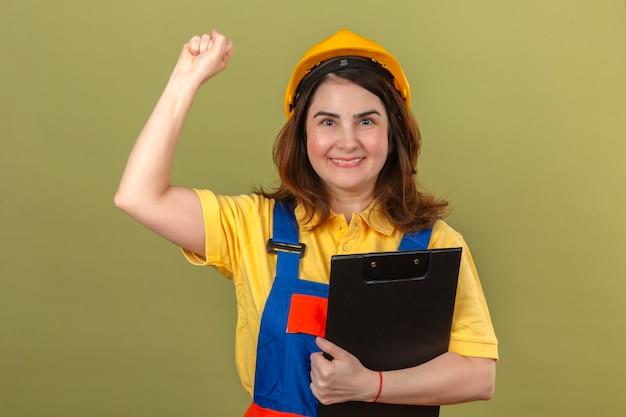 Builder woman wearing construction uniforme et casque de sécurité tenant le presse-papiers avec sourire levant le poing après un concept gagnant de la victoire sur mur vert isolé