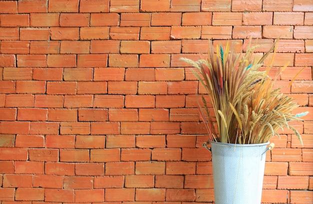 Buisson de fleurs d'herbe sèche dans un panier décoré au café contre le mur de briques rouges.