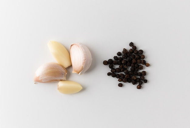 Bulbes d'ail gousses d'ail et morceaux d'ail cru avec du poivre noir ou des grains de poivre