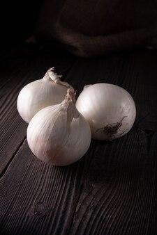 Bulbes d'oignons blancs sur une table en bois, aliments biologiques naturels.