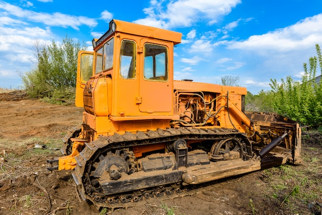 Bulldozer de chantier de construction industrielle nivellement et déplacement du sol pendant la construction de l'autoroute. bulldozer jaune sur un chantier de construction limoneux