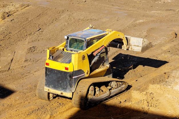 Le bulldozer déplace l'équipement de construction du sol en creusant le sol