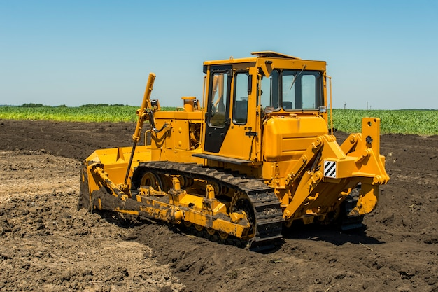 Bulldozer jaune avec tracteur à chenilles debout dans un champ