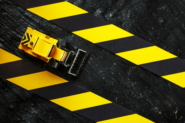 Bulldozer jouet jaune. ruban de clôture noir et jaune