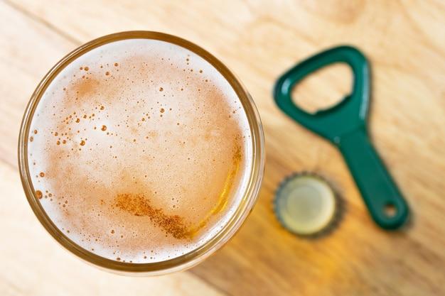 Bulle de bière froide et ouvreur vue de dessus sur table en bois