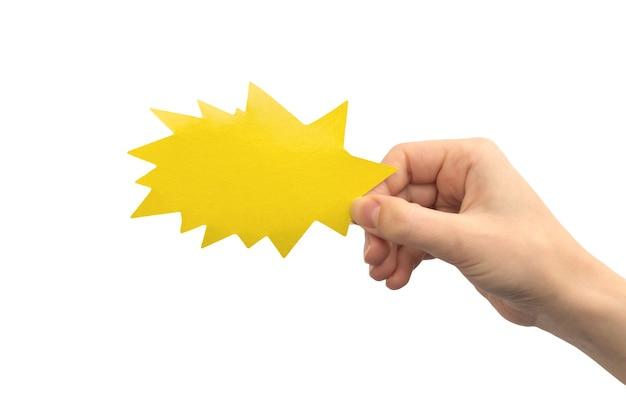 Bulle de dialogue en forme de foudre ou de flèche jaune à la main isolée sur fond blanc. donner des commentaires, concept de communication. photo de maquette de zone de texte en carton vide