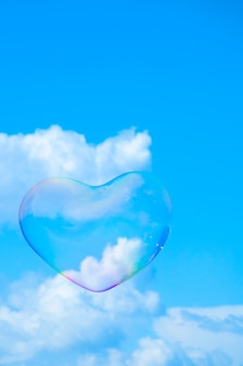 Bulle de savon en forme de coeur contre un ciel bleu avec des nuages blancs duveteux
