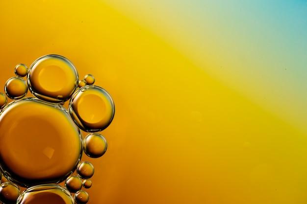 Bulles huileuses transparentes sur fond aqueux de l'espace de copie dynamique