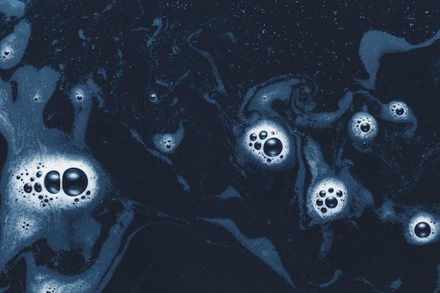 Bulles de mousse sur l'eau sombre