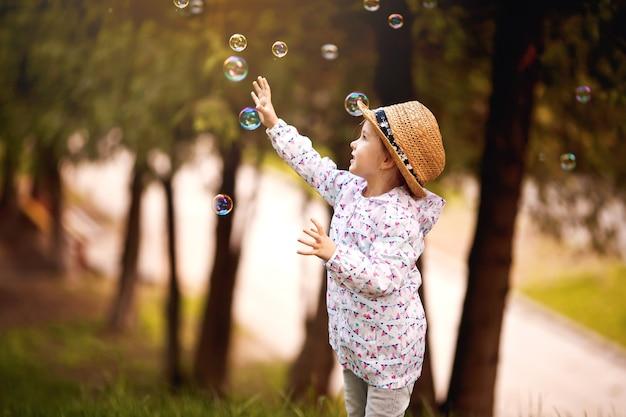Bulles de mousse ludique adorable fille mignonne heureuse dans une aire de jeux verte en été à l'extérieur. fille joyeuse drôle dans les temps de bonheur du parc.