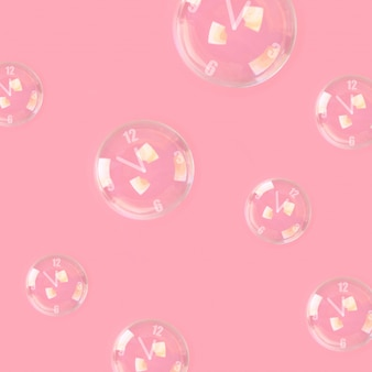 Des bulles de savon avec des flèches en forme d'horloge sur un fond rose pastel. minimalisme.