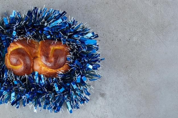 Bun sucré enveloppé de guirlande bleue sur marbre