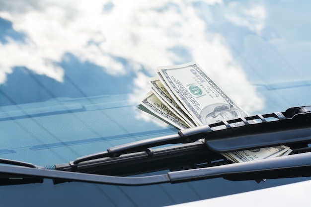 Bundle de billets en dollars américains à gauche sur une voiture sous l'essuie-glace de voiture sur un pare-brise