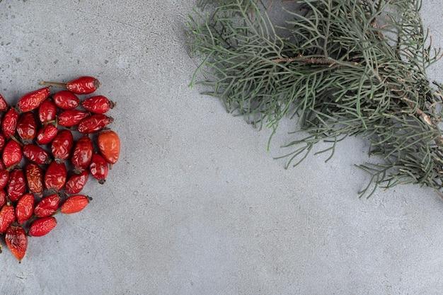 Bundle de dog-rose et une branche sur une surface en marbre
