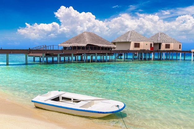 Bungalows sur pilotis et bateaux sur une île tropicale aux maldives
