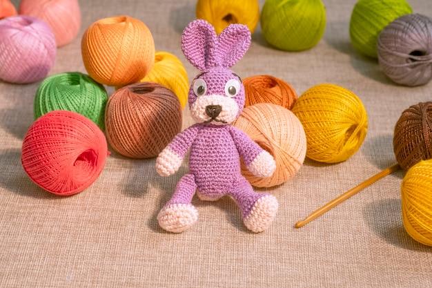 Bunny est un jouet avec des écheveaux de fils colorés à tricoter. loisirs couture, travaux manuels.