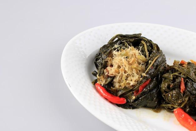 Buntil est un aliment traditionnel indonésien à base de feuilles de papaye/manioc farcies de noix de coco râpée, de petai cina et d'anchois. populaire dans la cuisine javanaise et sundaise, copy space