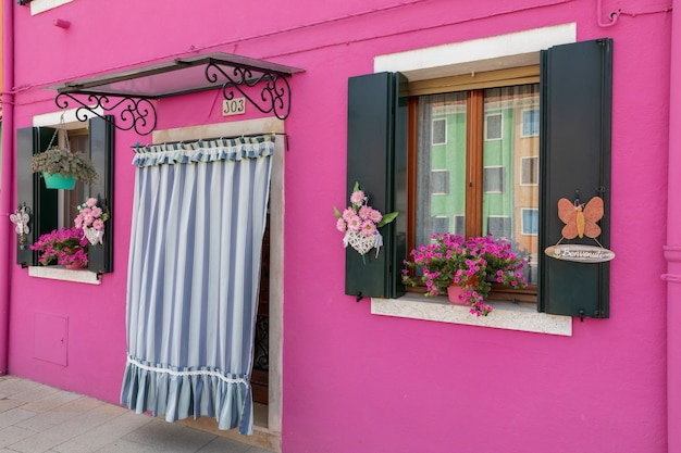 Burano, venise, italie - 2 juillet 2018 : vue panoramique sur les maisons aux couleurs vives de burano est une île de la lagune de venise. les gens marchent et se reposent dans les rues. journée ensoleillée d'été et ciel bleu