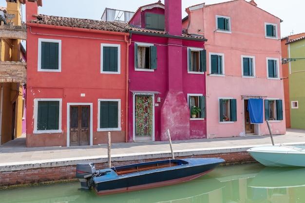 Burano, venise, italie - 2 juillet 2018 : vue panoramique sur les maisons aux couleurs vives et le canal d'eau avec des bateaux à burano, c'est une île de la lagune de venise. les gens marchent et se reposent dans les rues