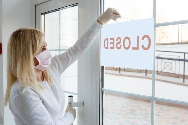 Le bureau d'affaires ou le magasin est fermé en raison de l'effet de la nouvelle pandémie de coronavirus (covid-19). personne non identifiée portant un masque suspendu signe fermé en arrière-plan sur la porte d'entrée.