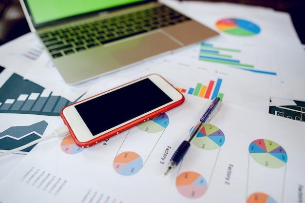 Bureau d'affaires avec ordinateur portable, bureau, stylo, papier, graphique de table