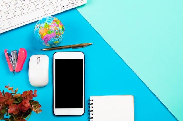 Bureau d'affaires avec papeterie et smartphone sur fond pastel