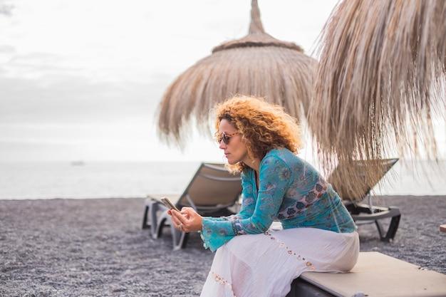 Bureau alternatif à la plage avec l'océan pour une belle femme d'âge moyen travaillant sur son smartphone assise sur un siège sous le parasol. vacances solitaire dame se connectant avec un ami