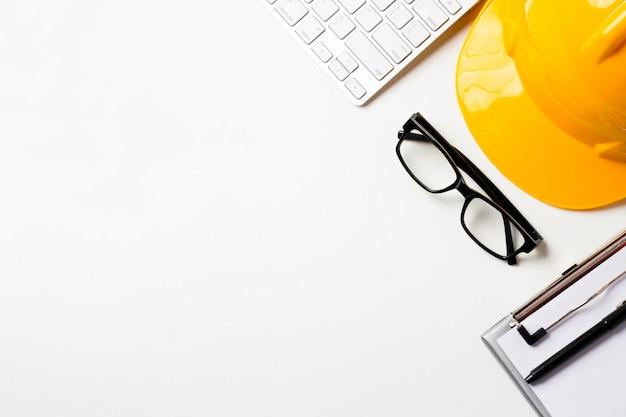 Bureau d'architecte avec outils, casque, ordinateur, lunettes et cahier.