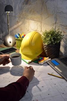 Bureau d'architecture avec dessins, ordinateur et personne de travail