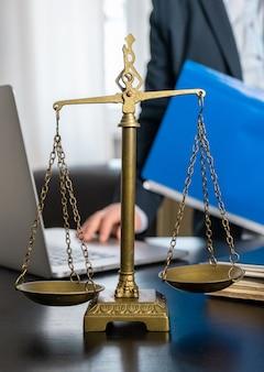 Bureau d'avocat avec balances, ordinateur portable et documents sur le lieu de travail.