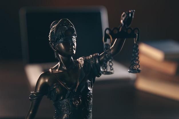 Bureau d'avocat statue de justice avec échelles et avocat travaillant sur un ordinateur portable conseil juridique et justice concept