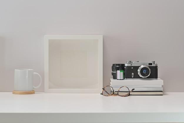 Bureau blanc avec un appareil photo vintage, des films, des affiches et un espace de copie scandinave
