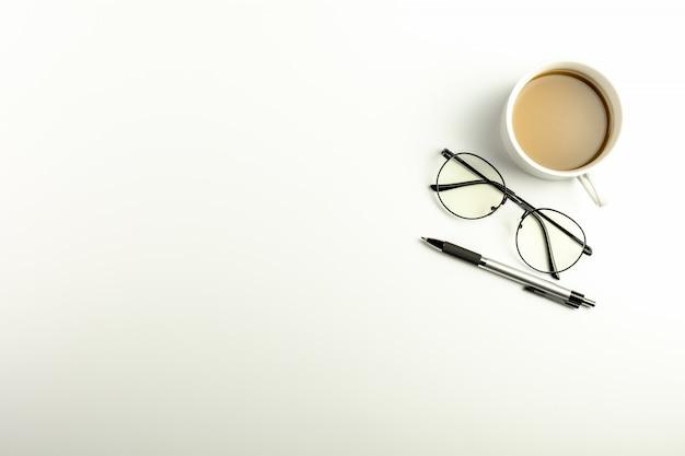 Bureau blanc avec des lunettes, un stylo et une tasse à café