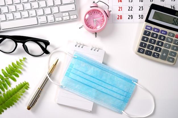 Bureau blanc avec masque médical et autre cahier de fournitures pour la saisie du texte à plat.