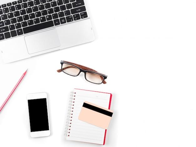 Bureau blanc minimal et moderne avec ordinateur portable, lunettes et autres fournitures
