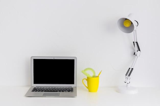 Bureau blanc avec ordinateur portable et lampe de lecture