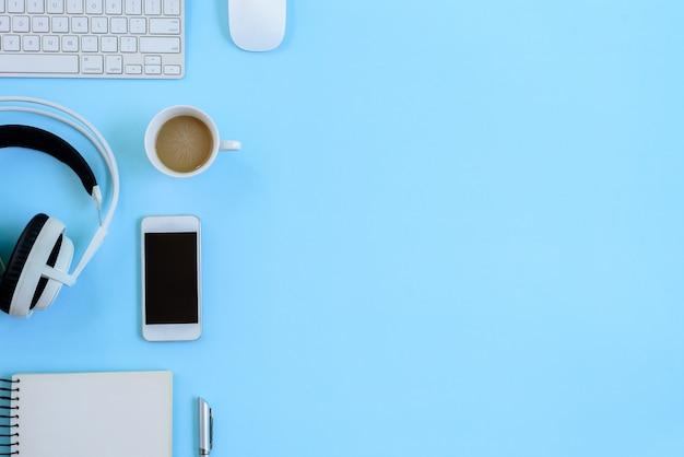 Le bureau bleu et son équipement pour travailler en vue de dessus et à plat s'étendent sur un fond bleu