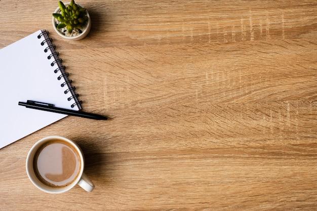 Bureau avec bloc-notes vierge et tasse de café sur une table en bois