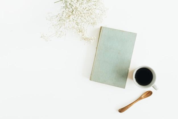 Bureau de blogger avec café, livre, fleurs sur une surface blanche