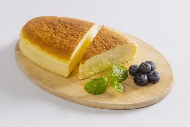 Bureau en bois avec cheesecake japonais et thé de l'après-midi, gros plan.