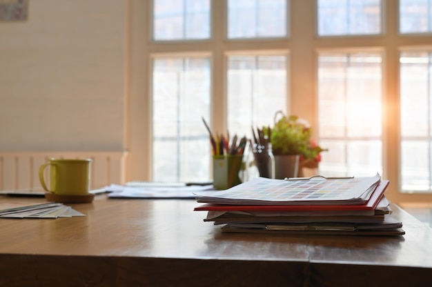 Bureau en bois créatif avec carte en papier de couleur et une tasse à café.