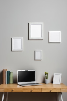Bureau en bois avec ordinateur portable et cadres photo