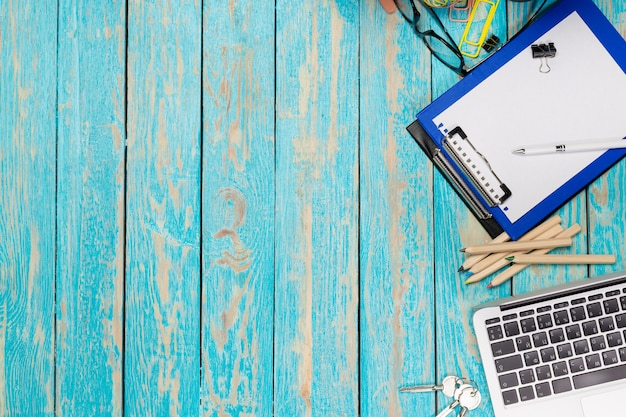 Bureau en bois avec ordinateur portable et fournitures de bureau. vue de dessus
